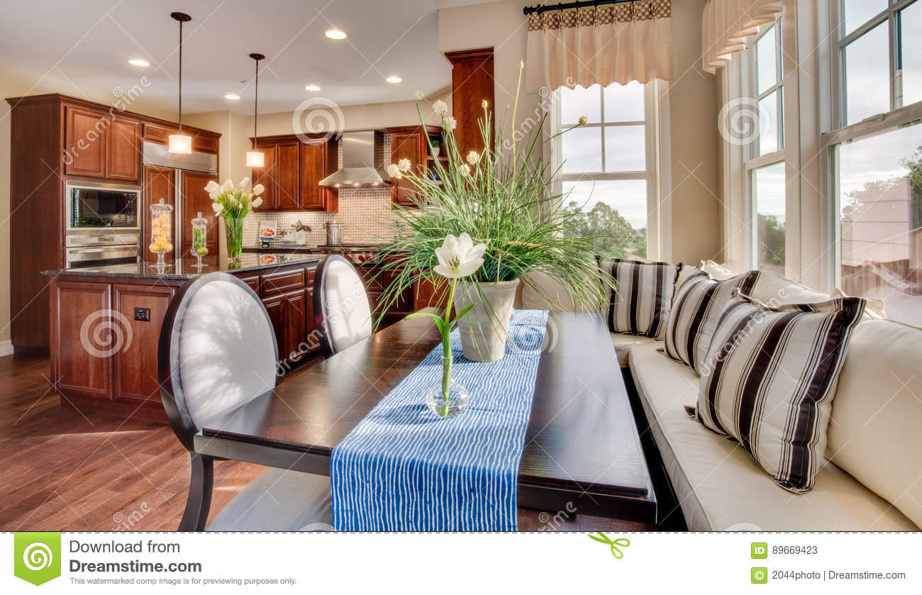 Flowers On Table And Island Counter. Wood Floor. Chair And Bench Seating.  Sunshine Coming In Through Windows. Stainless Steel Appliances.