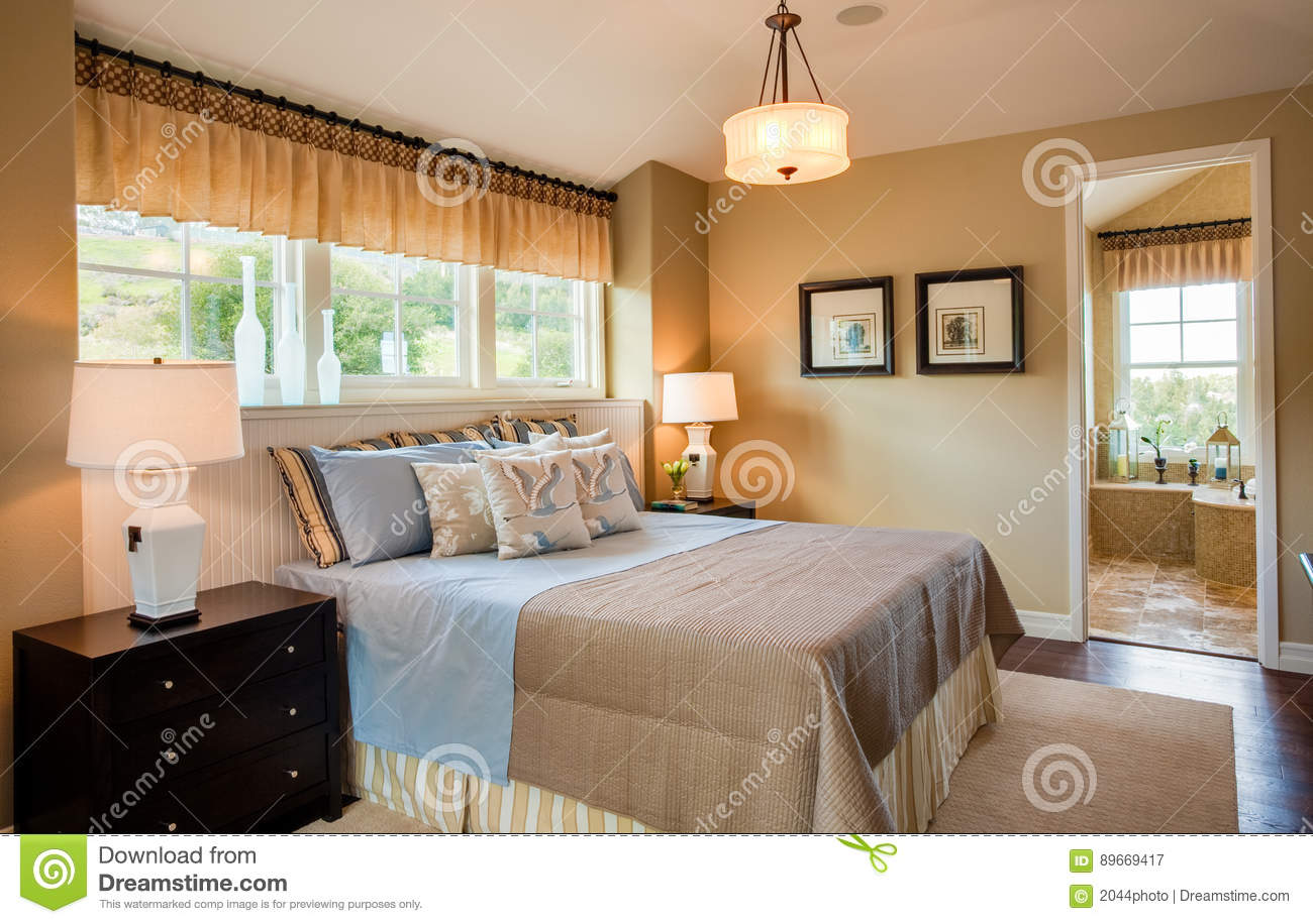 Residential home master bedroom bathroom in background windows with view tan walls blue linens wood floor with area rug under bed