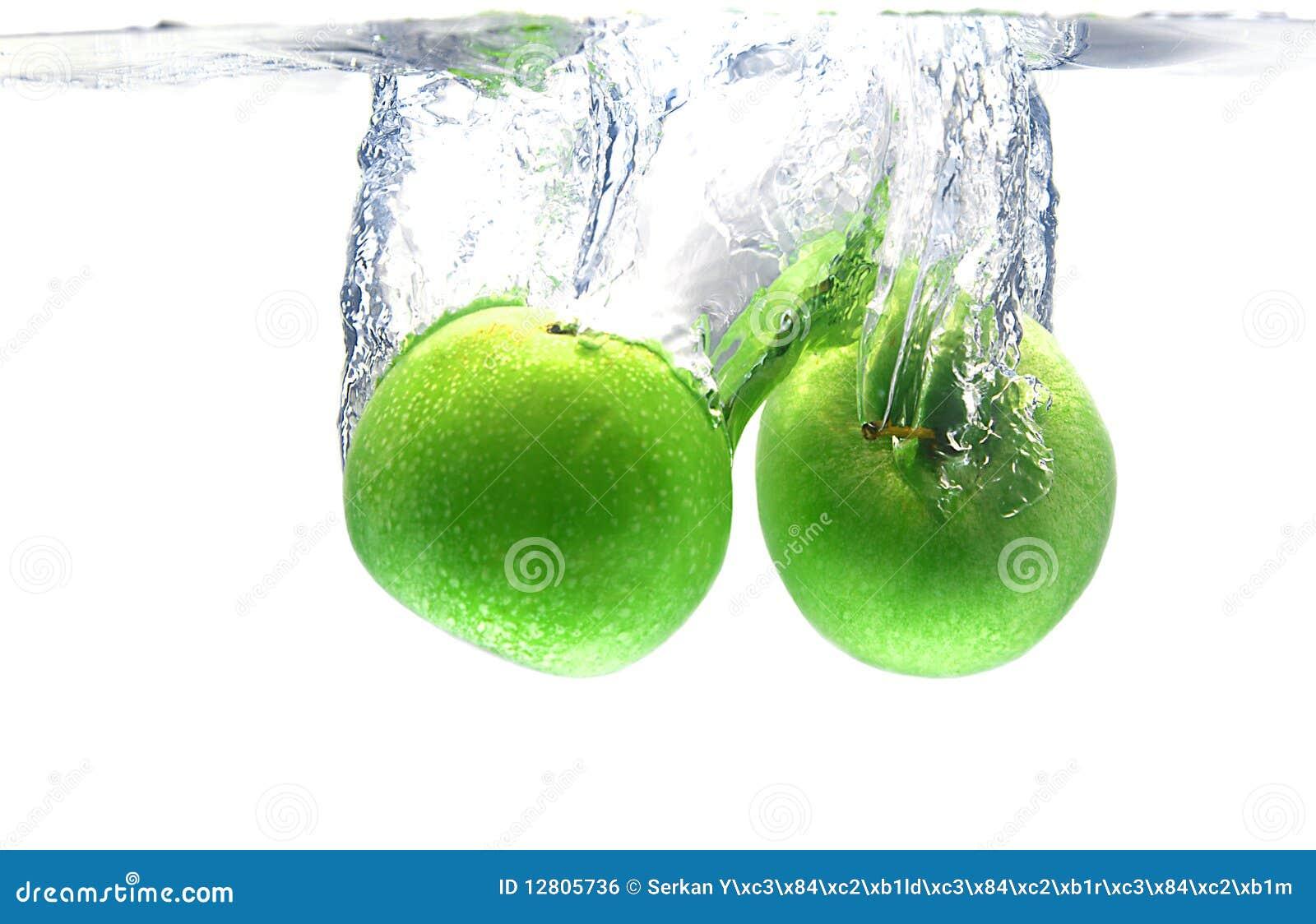 Respingo verde da maçã sobre o branco