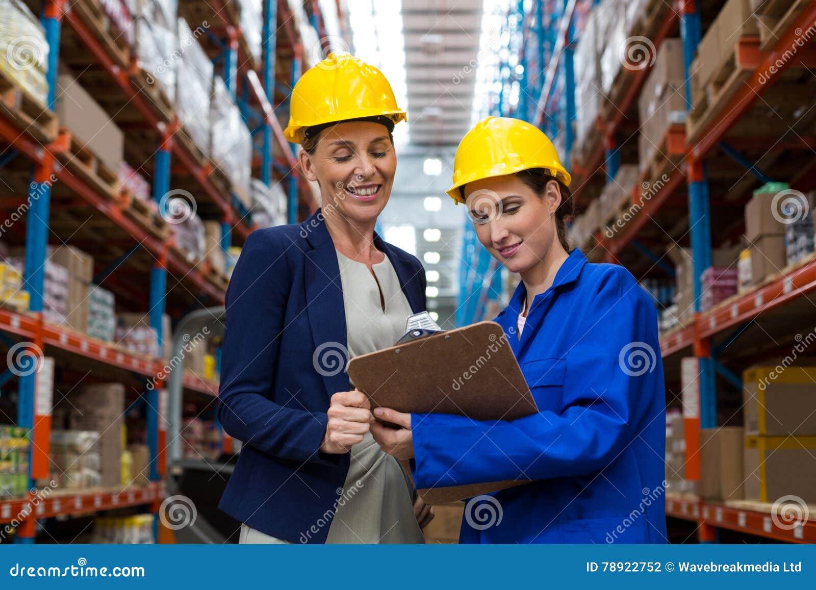 Responsabile e lavoratore del magazzino che discutono con la lavagna per appunti