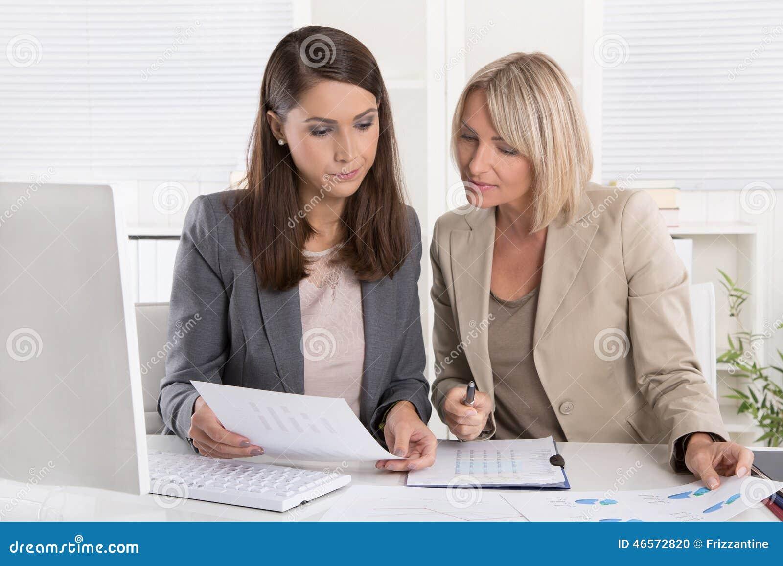 Responsabili senior e minori femminili che si siedono al togeth di lavoro dello scrittorio