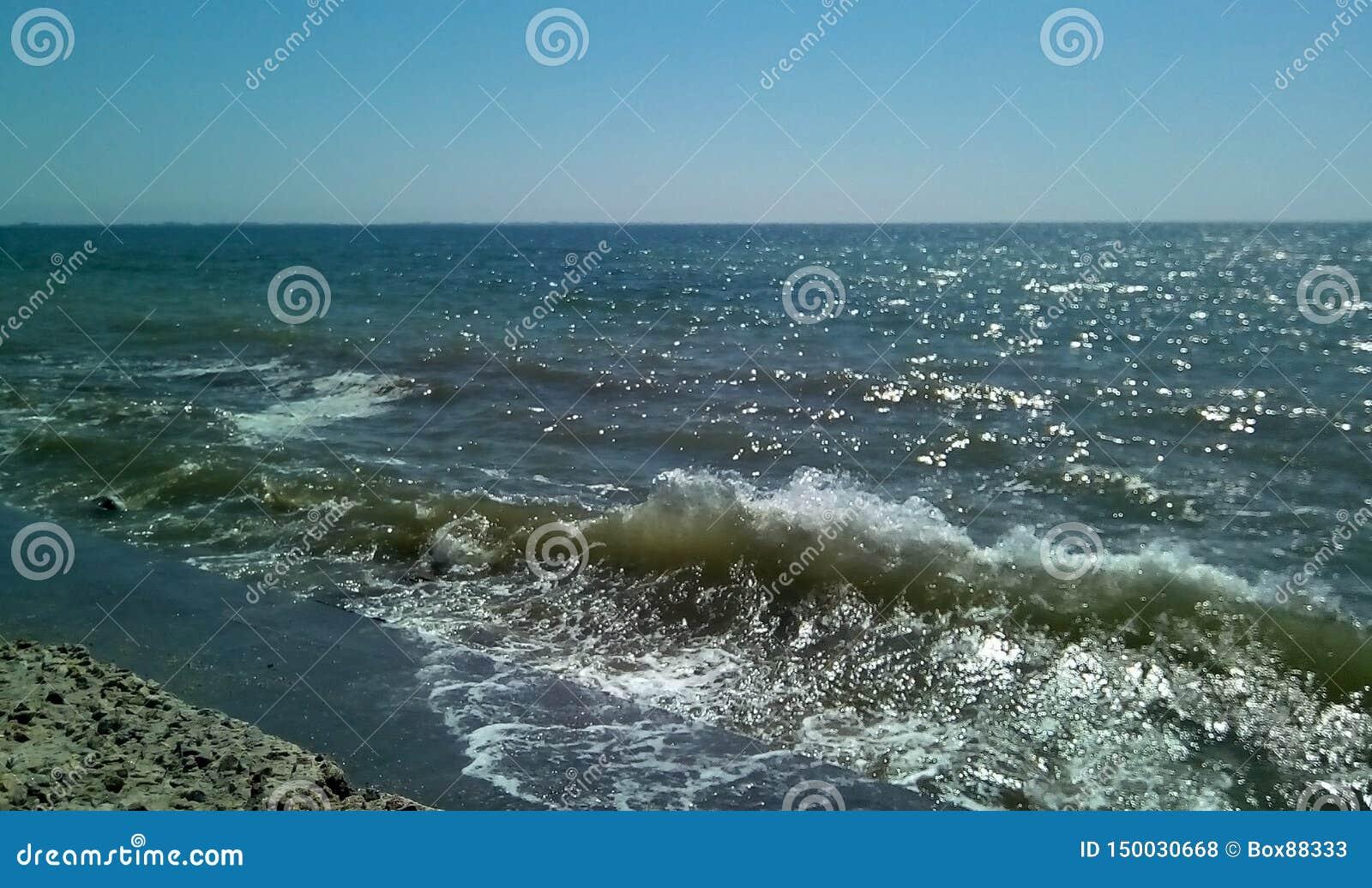 Ressaca do mar em um dia ensolarado Vista do mar da represa