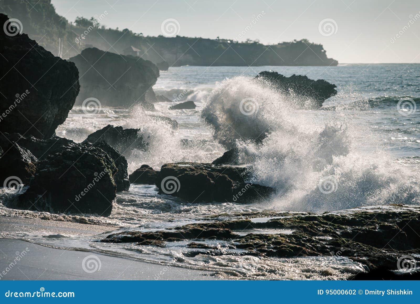 Ressacs se brisant sur les roches dans le coucher du soleil