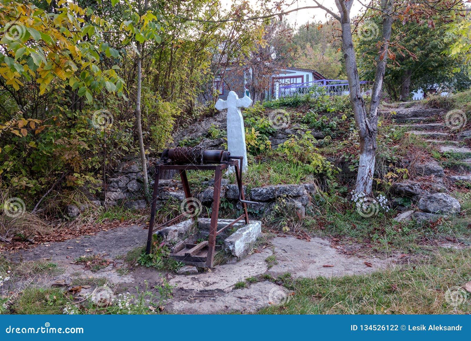Ressort saint de l eau vivante, murs couverts de mousse, automne Le puits d eau saint avec une croix a bien alimenté l eau de sou