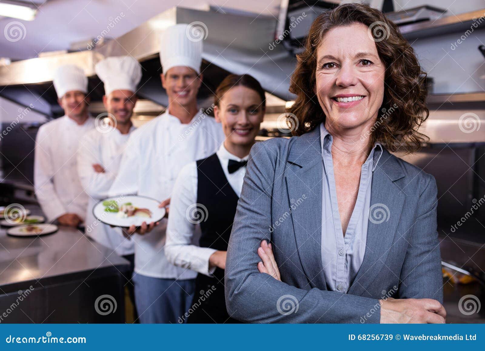 Restauracyjny kierownik pozuje przed drużyną personel