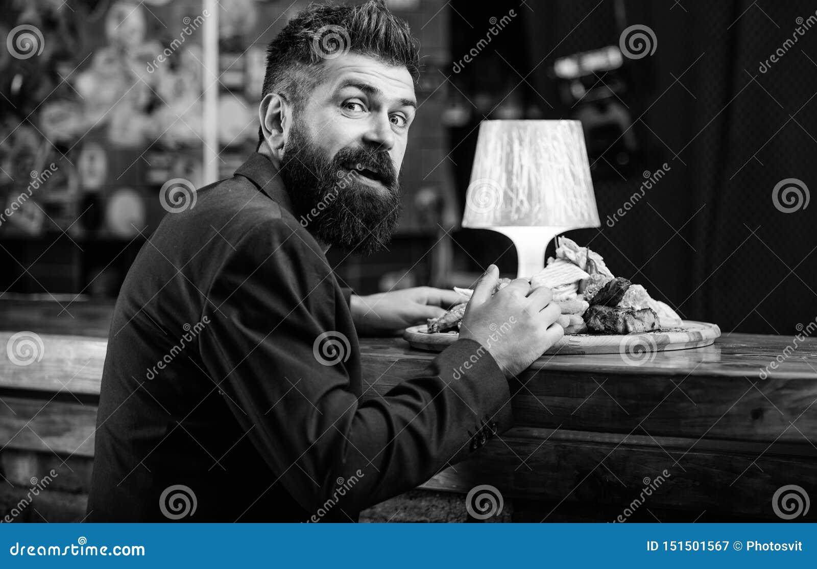 Restauracyjny klient Modnisia formalny kostium siedzi przy baru kontuarem Obs?uguje otrzymywaj?cego posi?ek z sma??cymi kartoflan