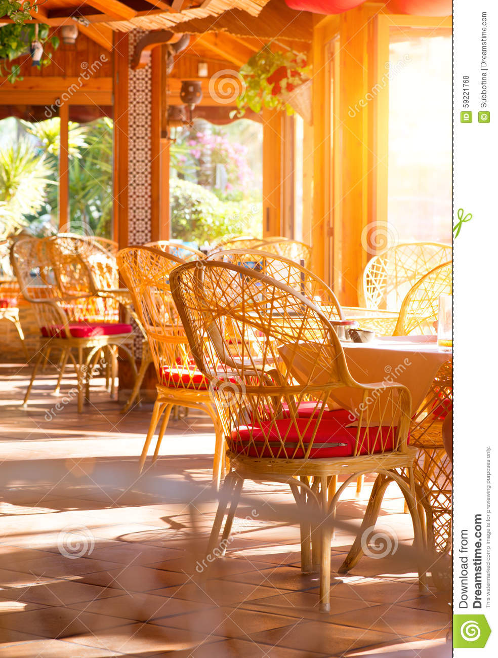 Restaurant interior. Summer coffee terrace with tables and wicker chairs