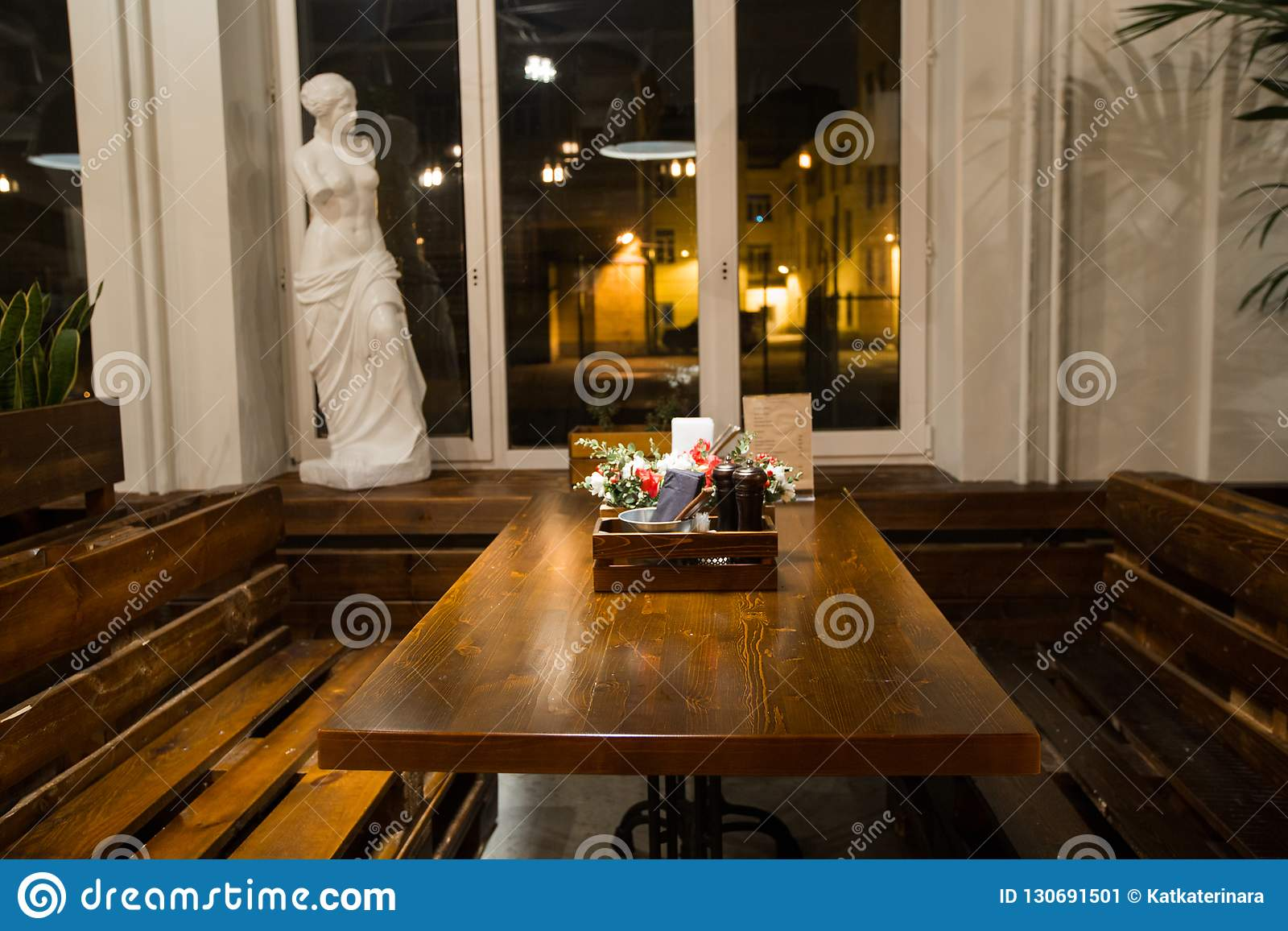 Restaurant interior with wooden tables and flowers and green plants