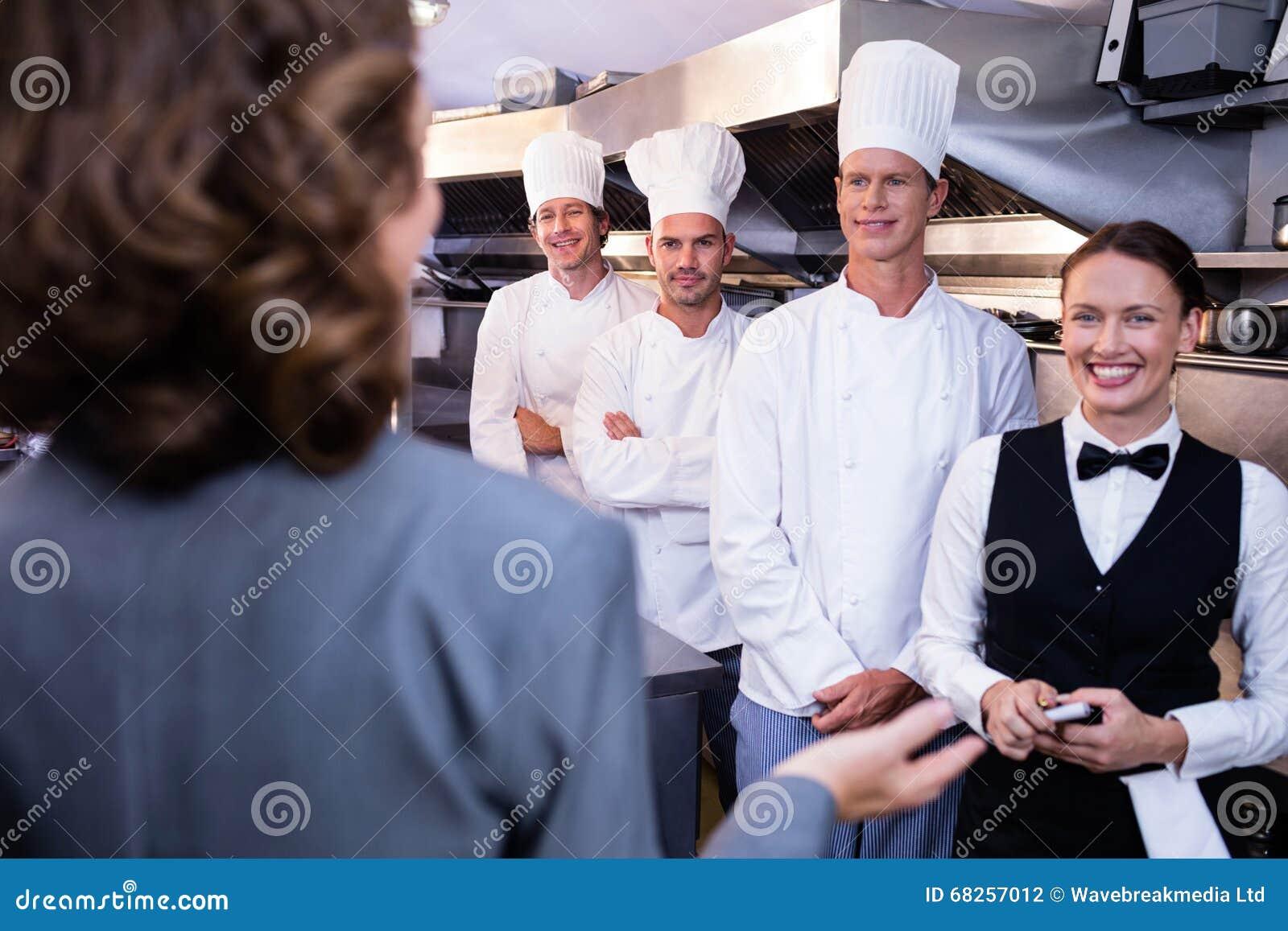 Restaurant Kitchen Staff restaurant manager briefing to his kitchen staff stock photo