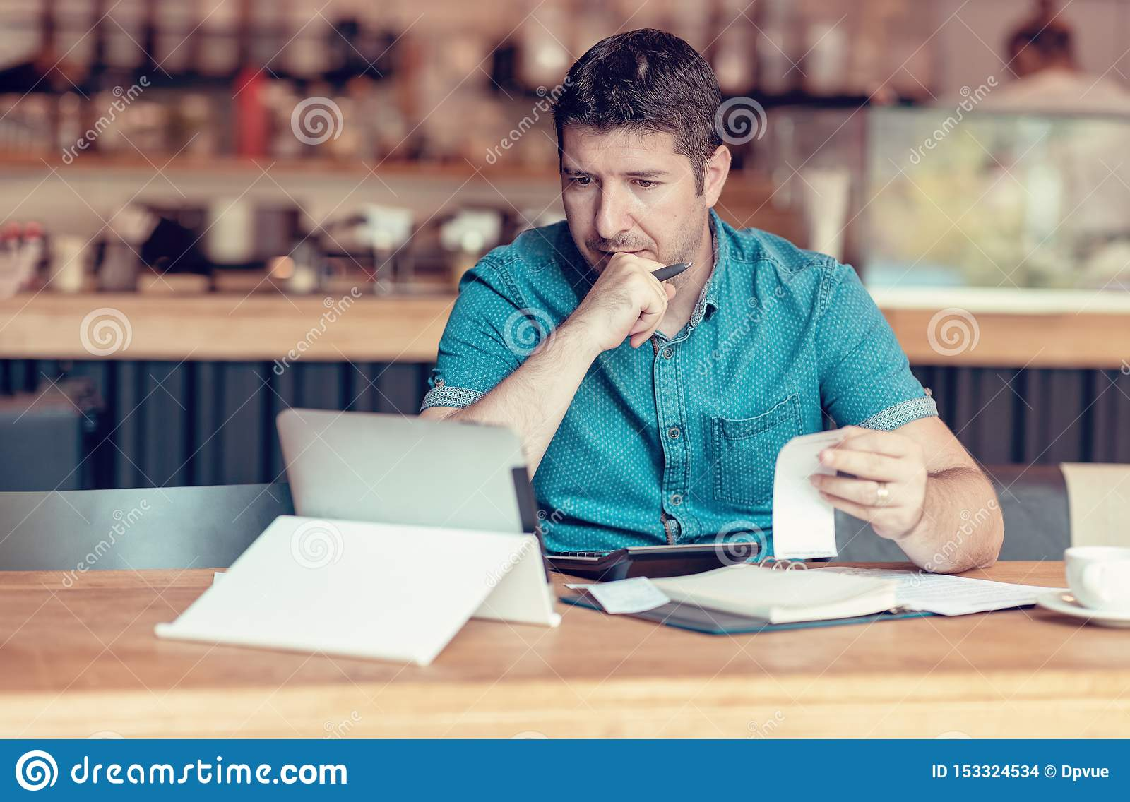 Restaurant owner checking monthly reports on a tablet, bills and expenses of his small business. Start-up entrepreneur concerned