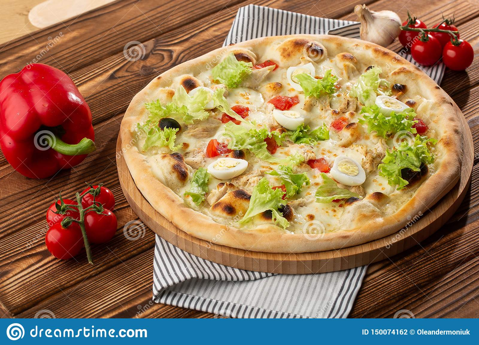 Delicious pizza Caesar style with white sauce, chicken, parmesan, egg, cherry tomatoes and fresh lettuce at wooden background.