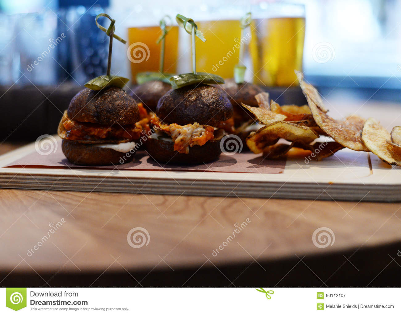 Sliders Burgers Plated On Restaurant Table With Chips And Drinks