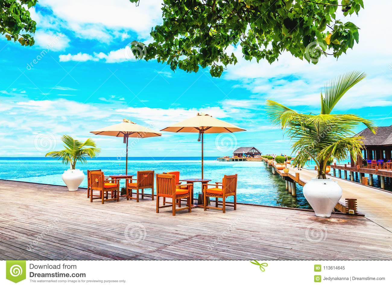 Restaurant with sun umbrellas on a wooden pier against the azure water of the ocean