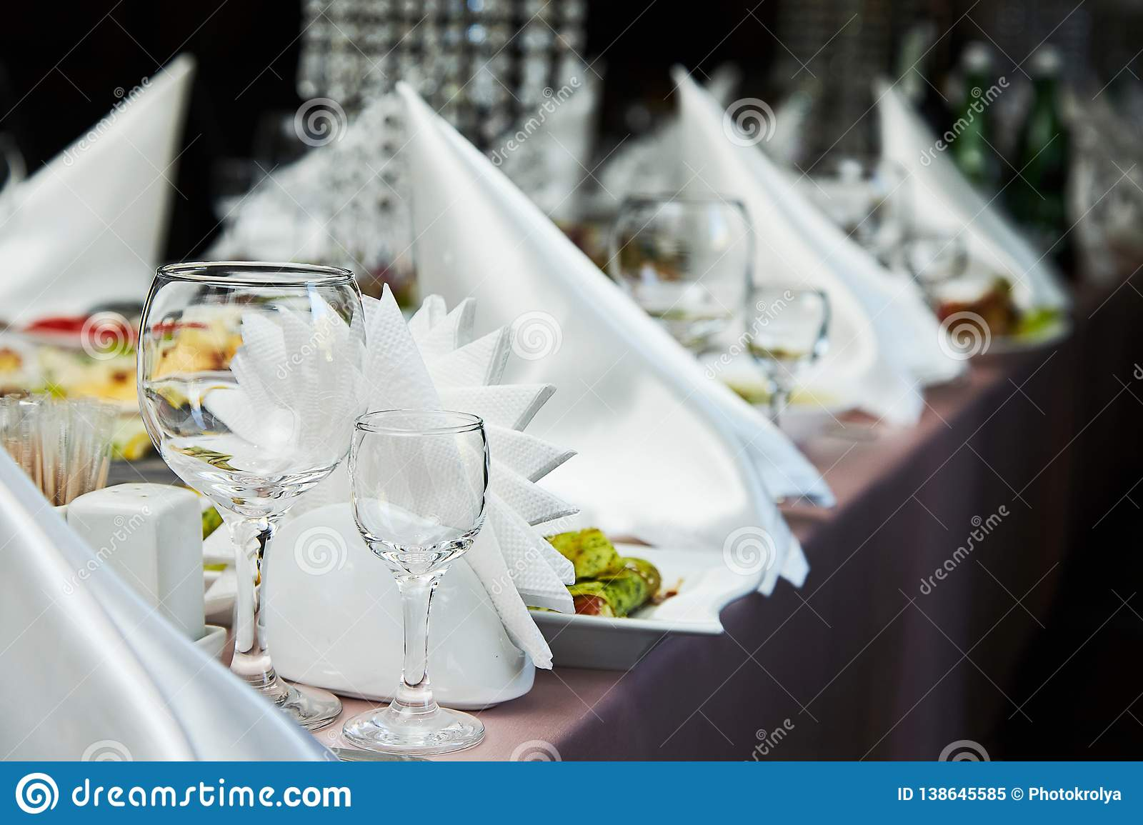 Restaurant table setting decor with glasses for wine. Different meals for the guests.
