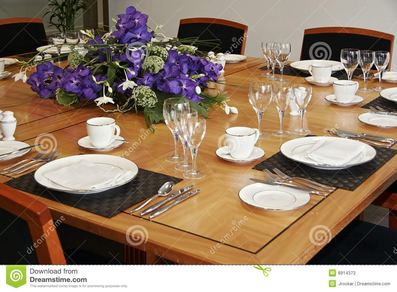 Restaurant table setup with cut flowers stock image