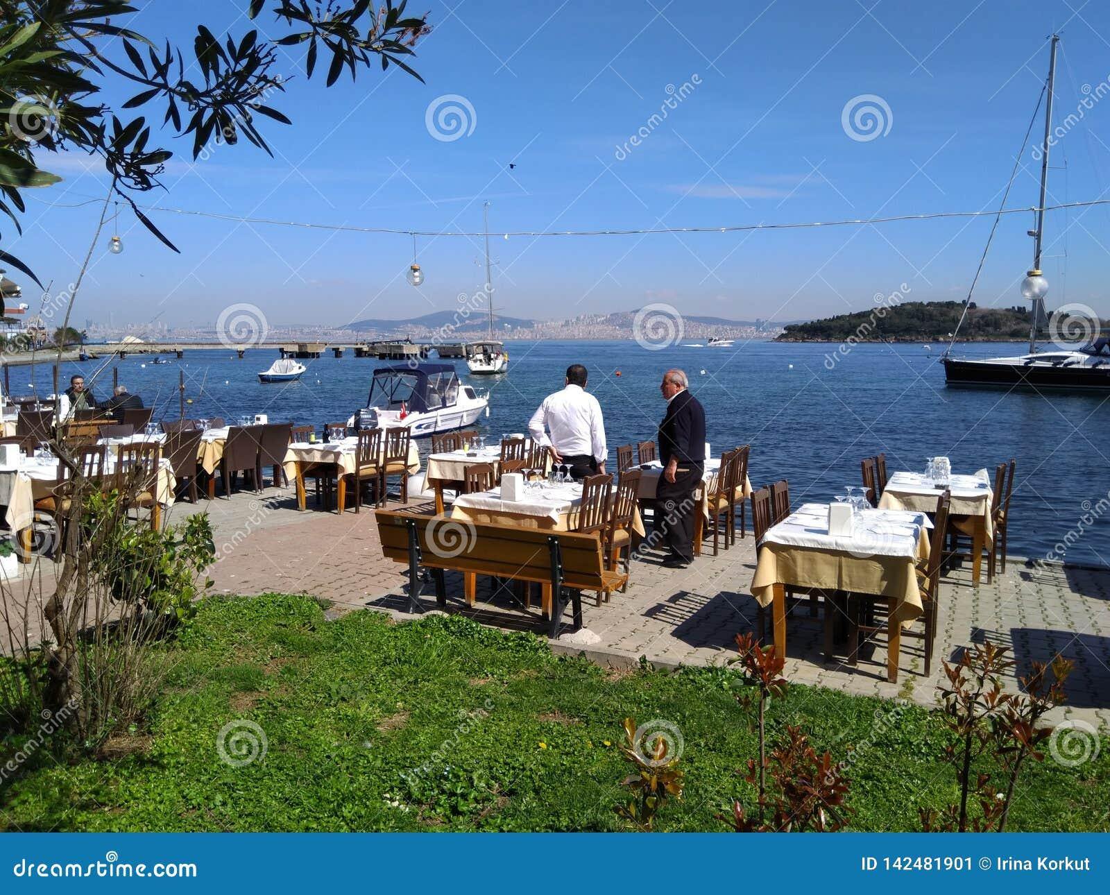 Restaurante exterior muito agradável com iate e opinião do mar