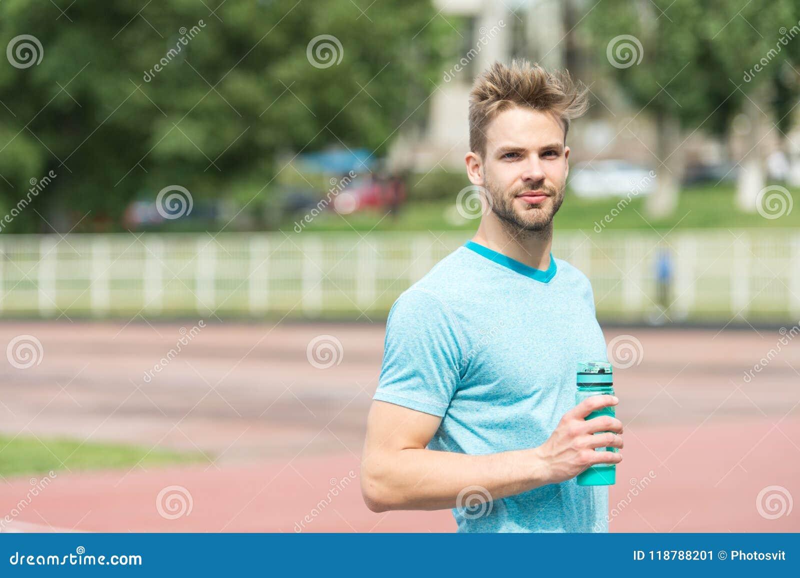Rester hydraté L aspect sportif d homme tient la bouteille d eau continuent à rester hydraté pendant la formation Vêtements de sp