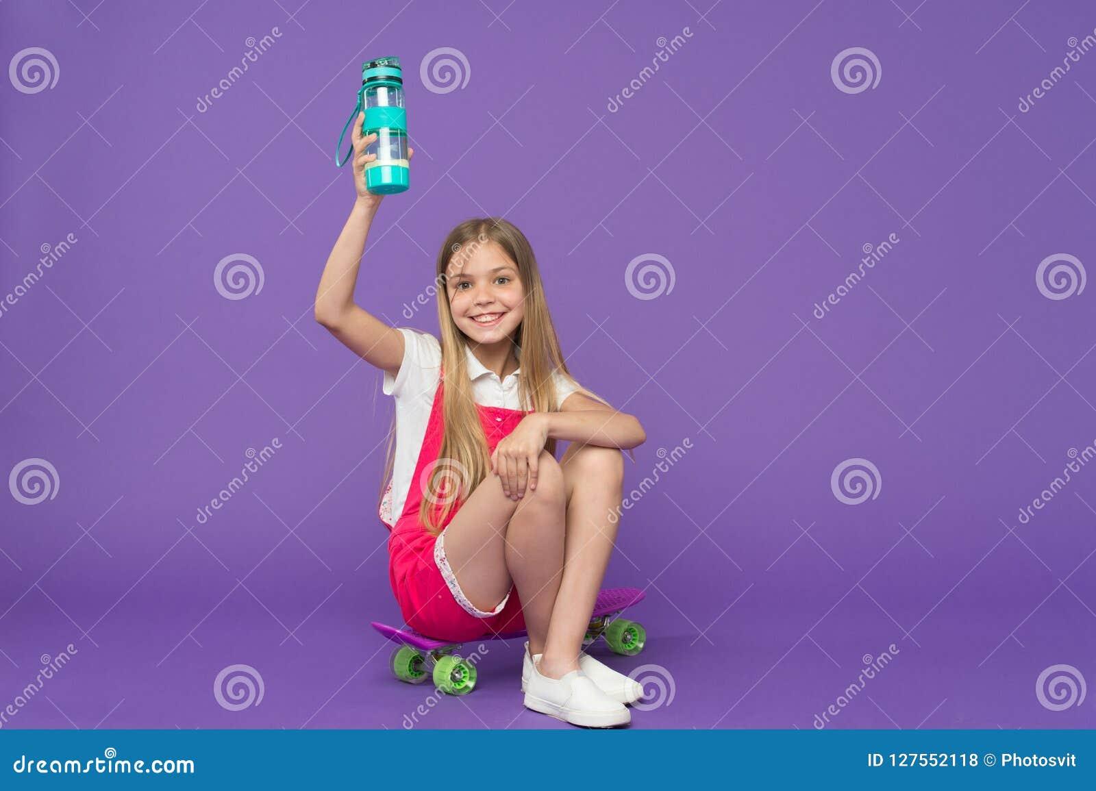Rester hydraté Le visage heureux de fille se tient avec la bouteille d eau tandis que reposez le fond de violette de panneau de p