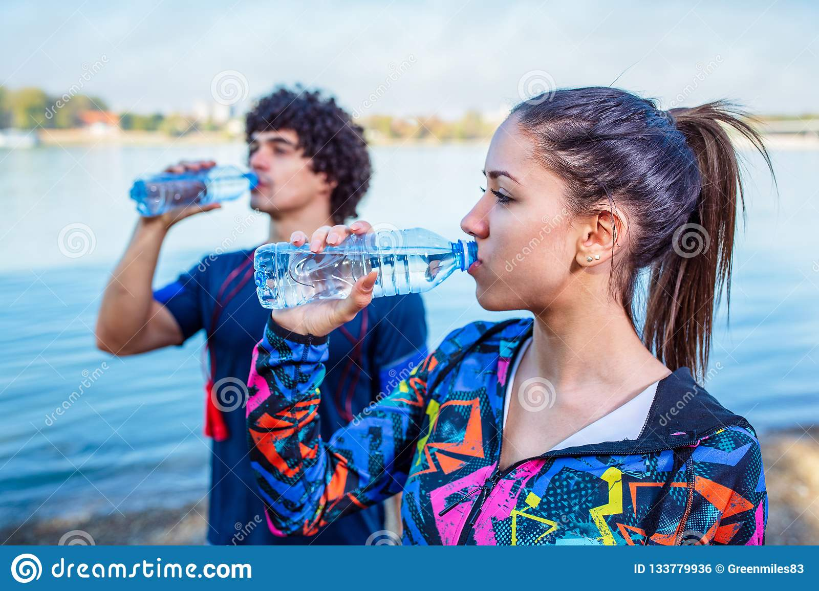 Resting After Workout-Woman drinks water to replenish energy