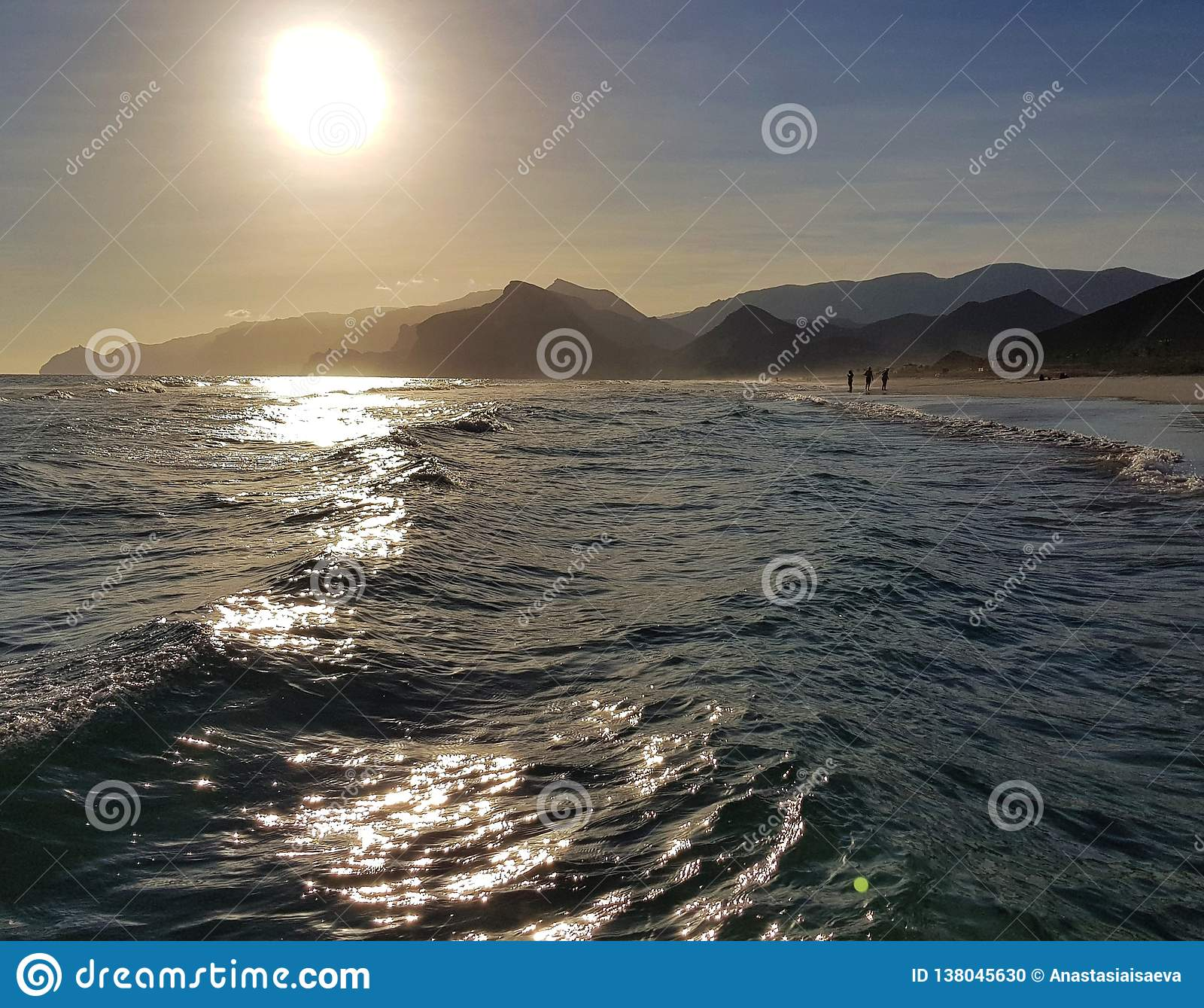 Restless sea waves with sunlight reflections and mountains