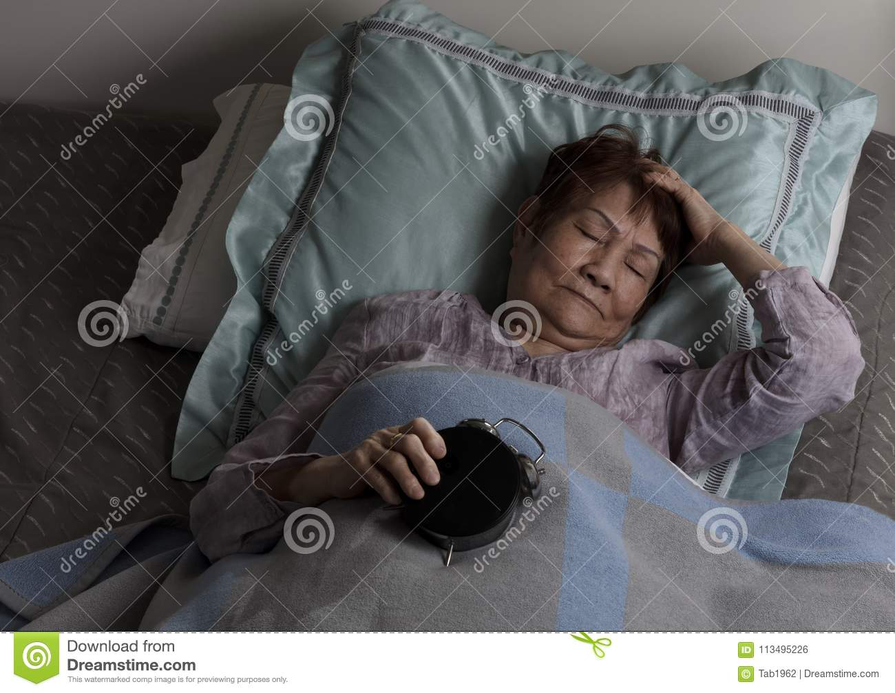 Restless senior woman holding alarm clock upside down during nighttime while in bed