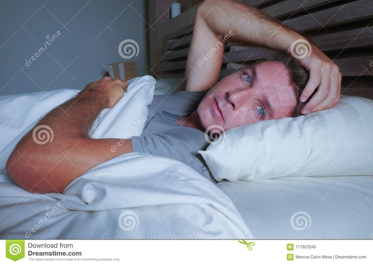 Restless worried young attractive man awake at night lying on bed sleepless with eyes wide opened suffering insomnia sleeping diso