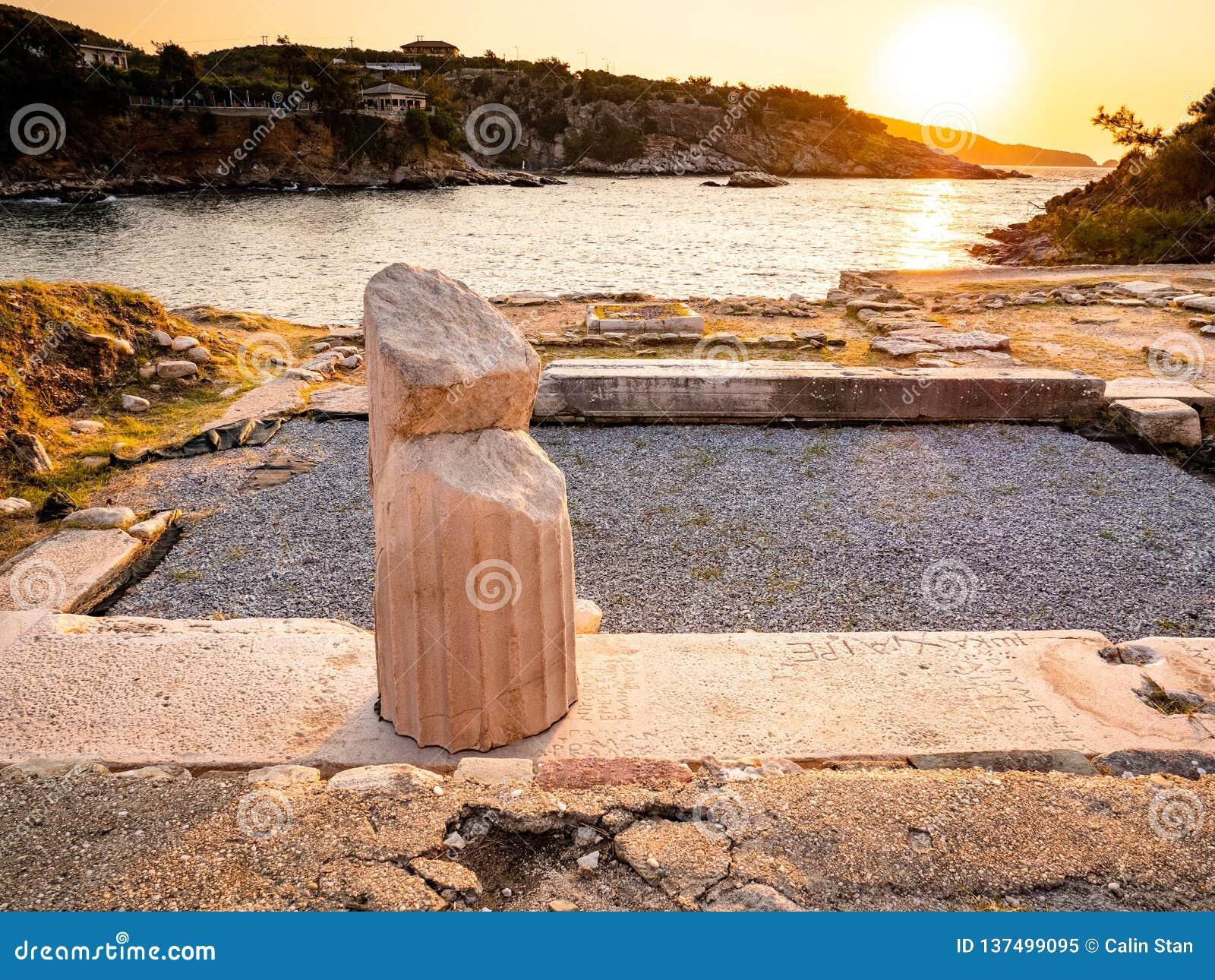 Restna av Aliki det forntida marmorvillebrådet och marmorport, i soluppgångljus