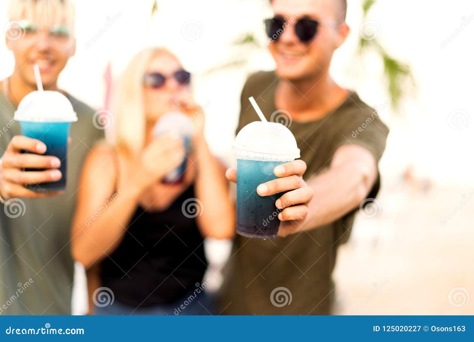 Resto allegro della società di tre amici su una spiaggia e su un drin tropicali