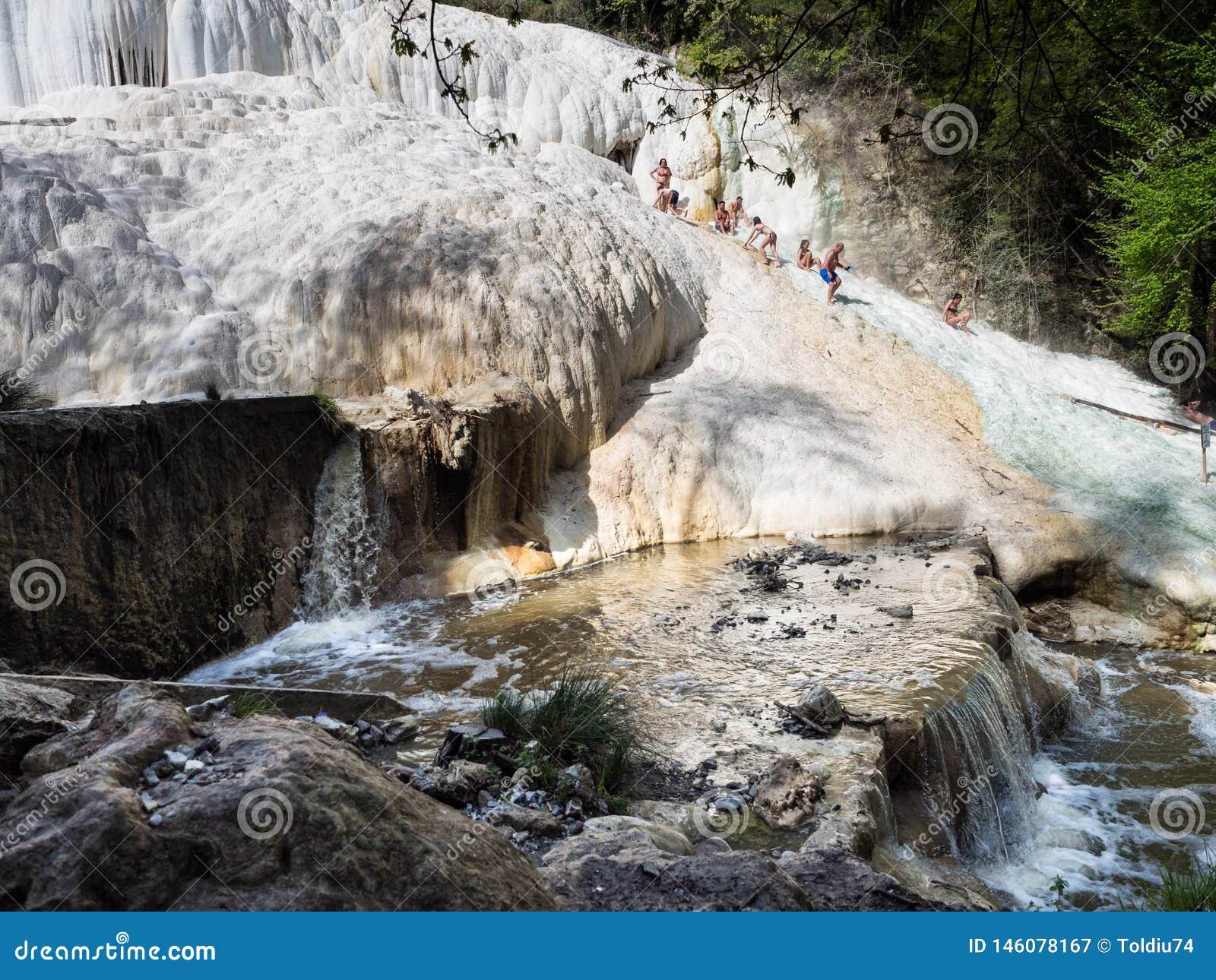 Resto de la gente en las cascadas termales de la sal de las primaveras minerales de Bagni San Filippo en un día soleado