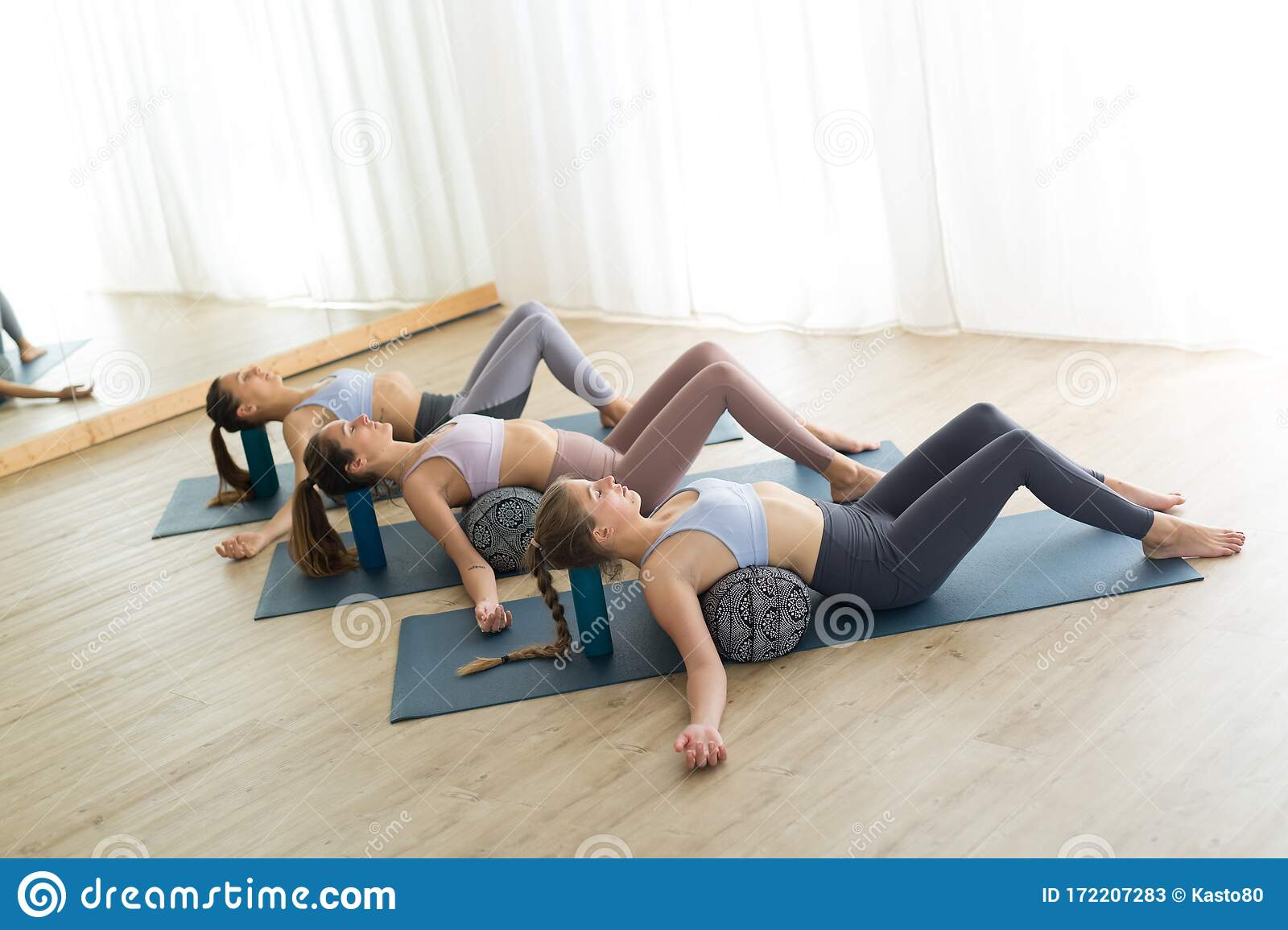 Restorative Yoga With A Bolster. Group Of Three Young Sporty