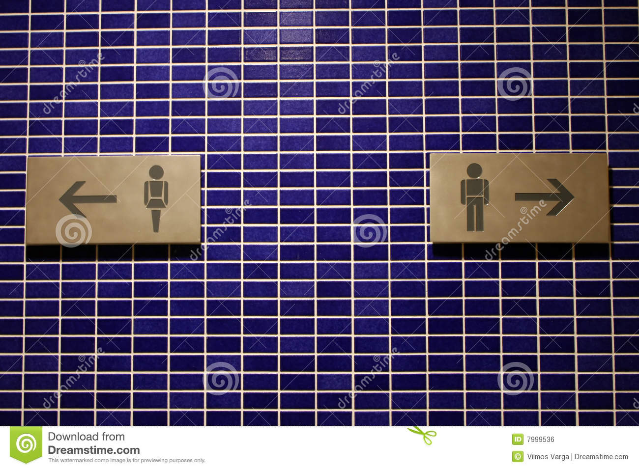 Blue tiled wall with restroom signs and arrows