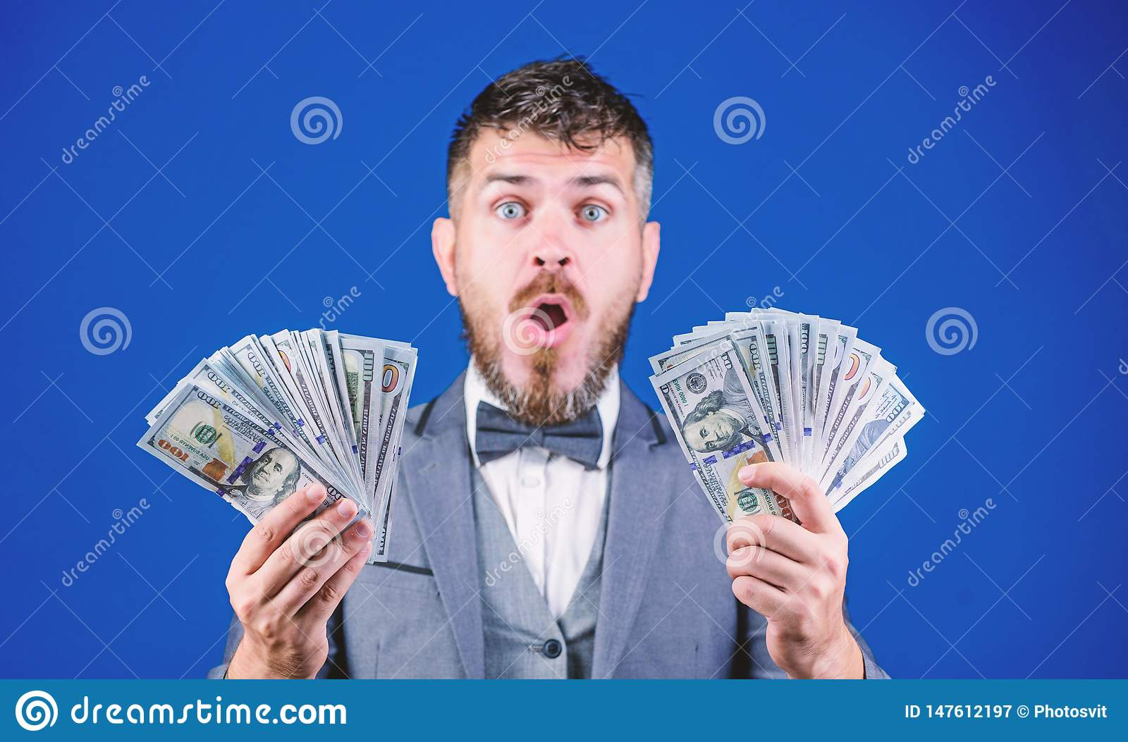 The result surpassed all his hopes. Bearded man holding cash money. Rich businessman with us dollars banknotes. Currency