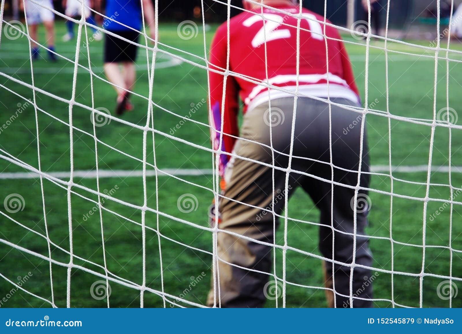 Rete dietro il portiere in uniforme rossa Ognuno gioca a calcio