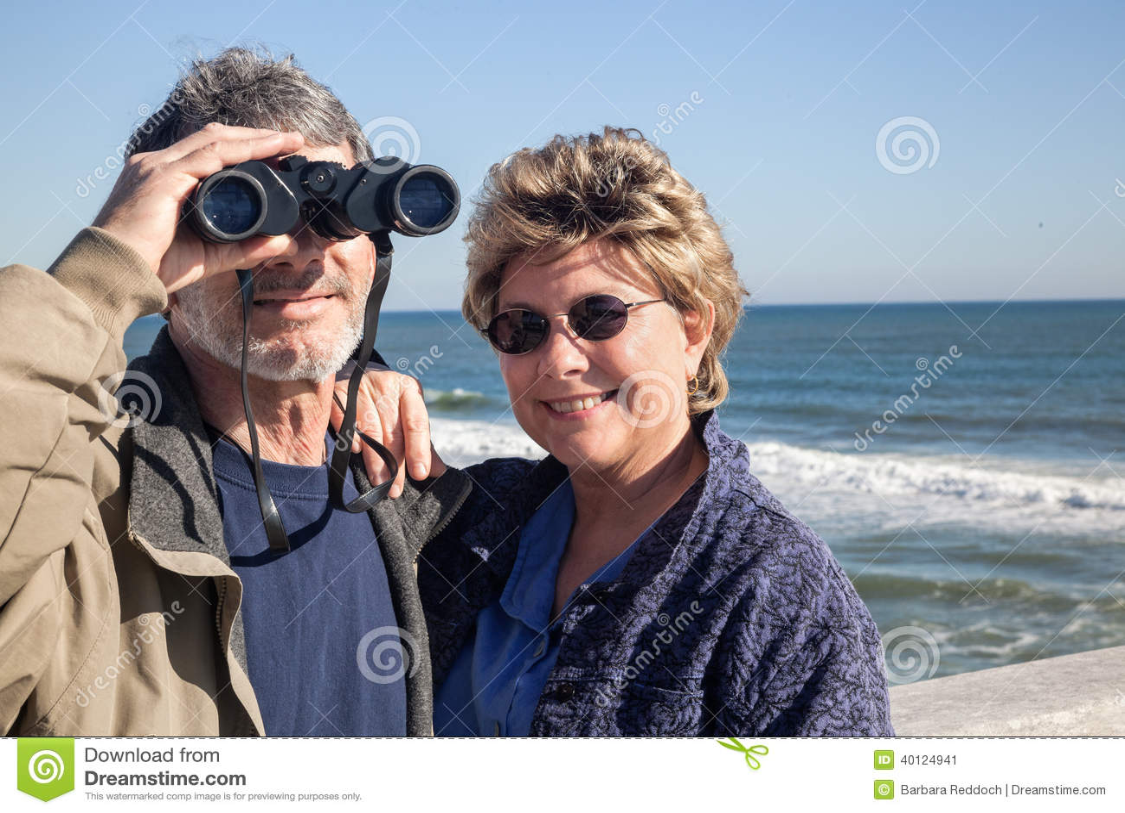 Retired couple on beach vacation with binoculars