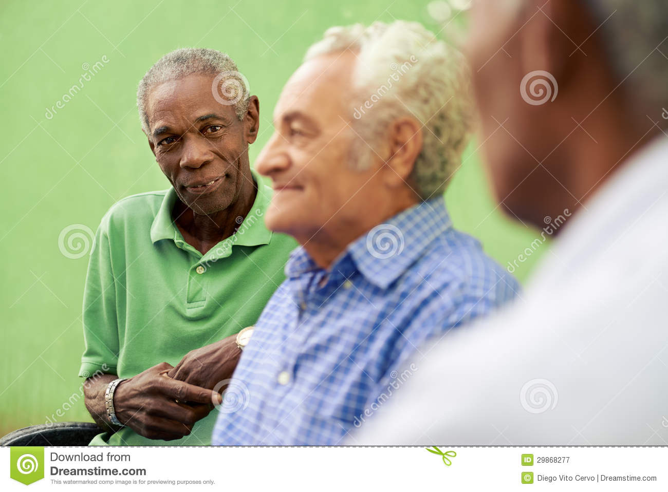 group of old black and caucasian men talking in park stock