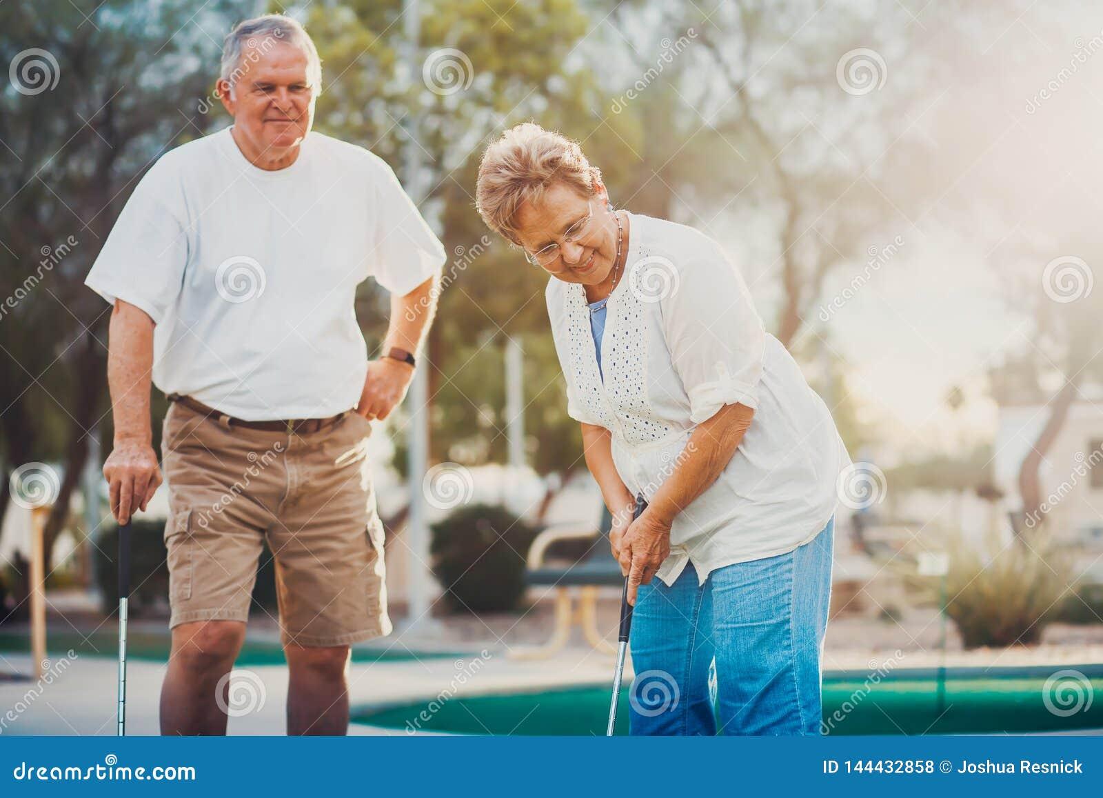 Retired heiratete die älteren Paare, die zusammen Minigolf spielen