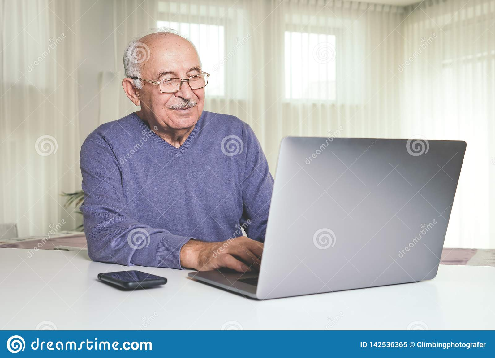 Retired man using computer technologies at home