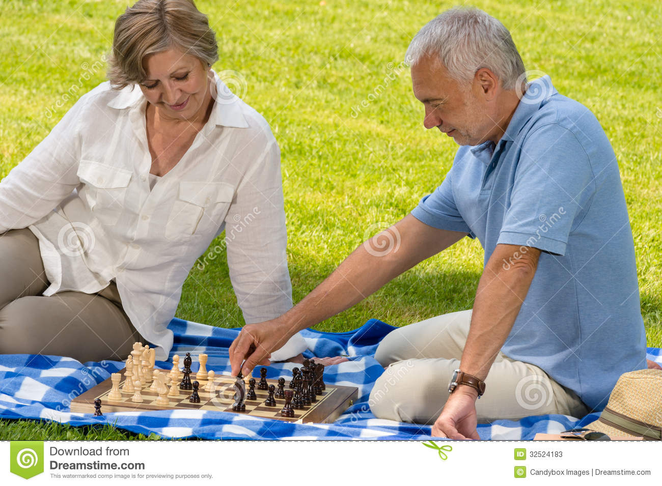 Retired senior couple playing chess in park