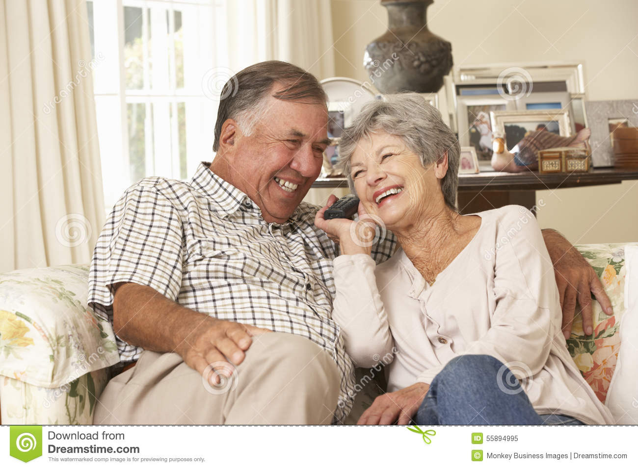 Retired senior couple sitting on sofa talking on phone at for House plans for retired couples