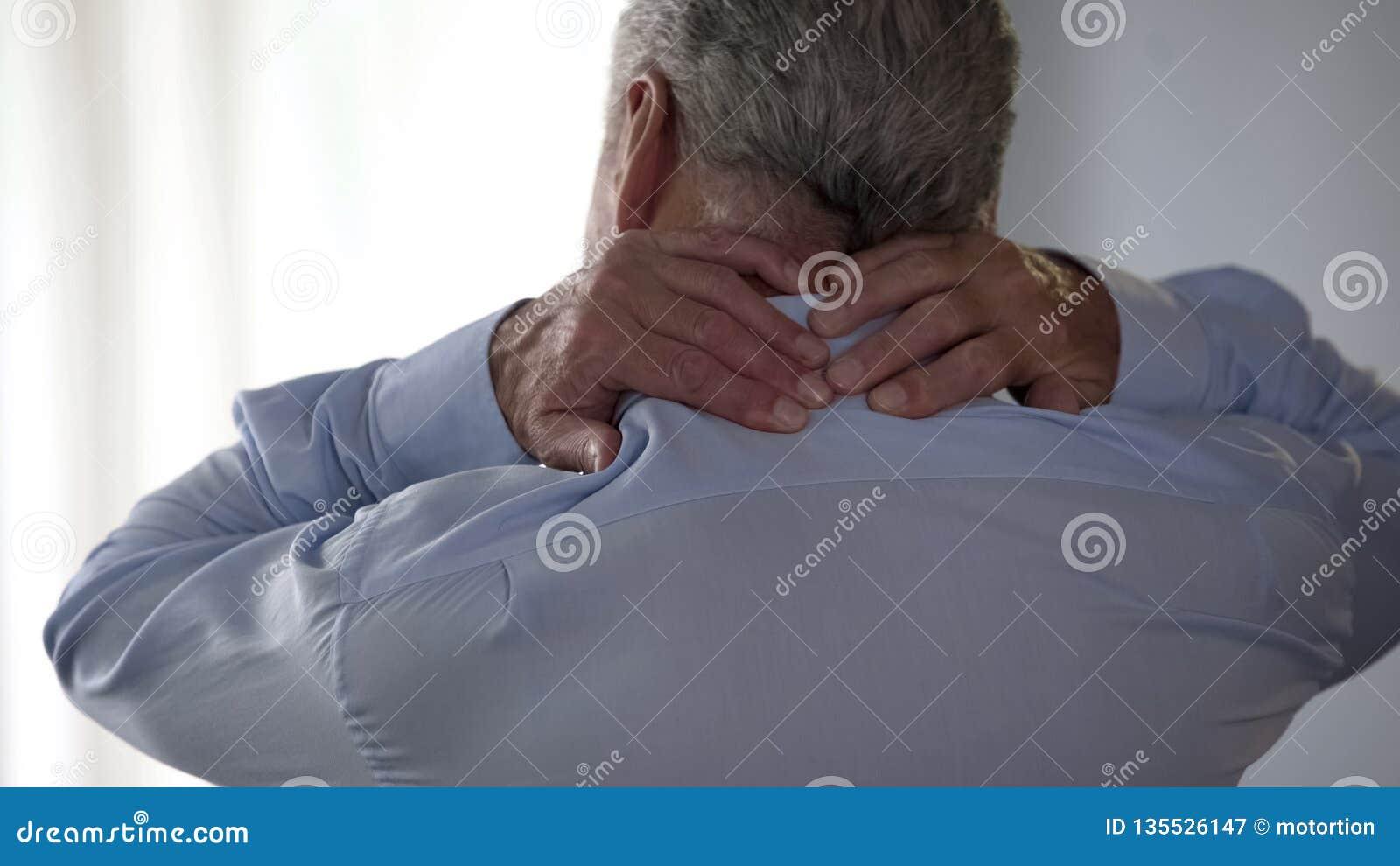Retiree man rubbing back of his neck, standing backwards, office desk worker