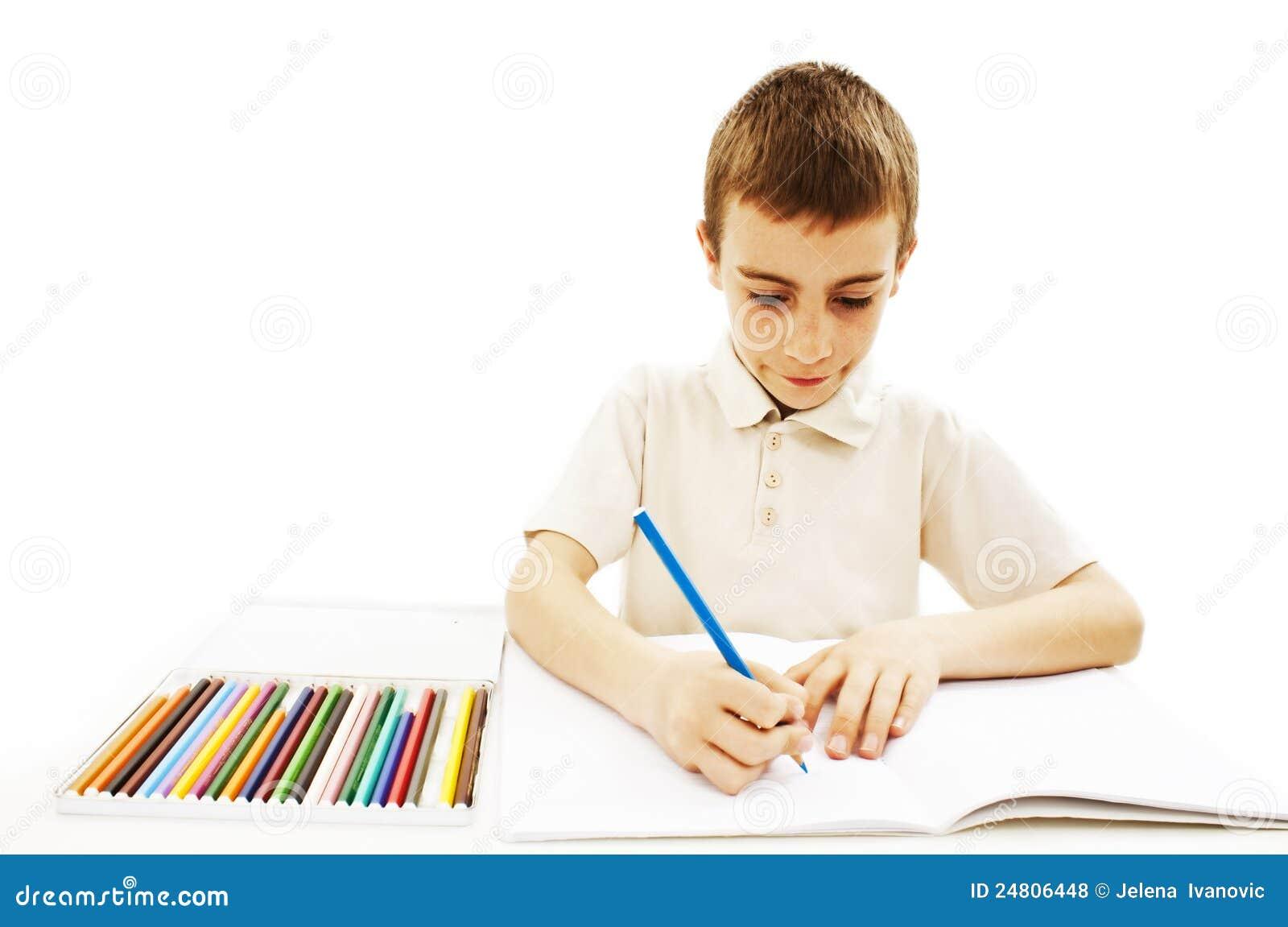 Retrait absorbé de petit garçon avec les crayons colorés