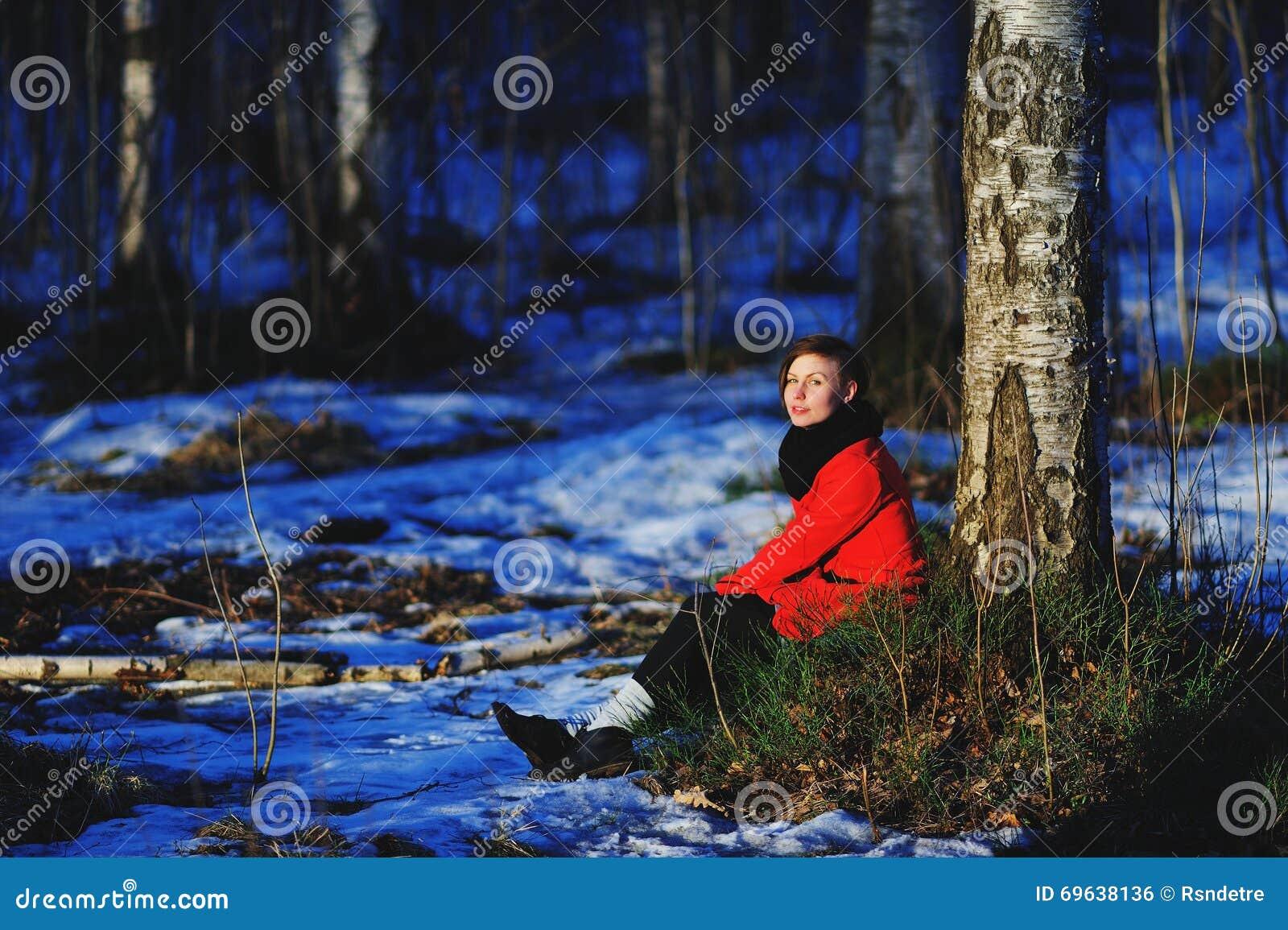 Retrato adiantado da mola da moça séria atrativa bonito com o lenço do calor do cabelo escuro e o revestimento vermelho que olham