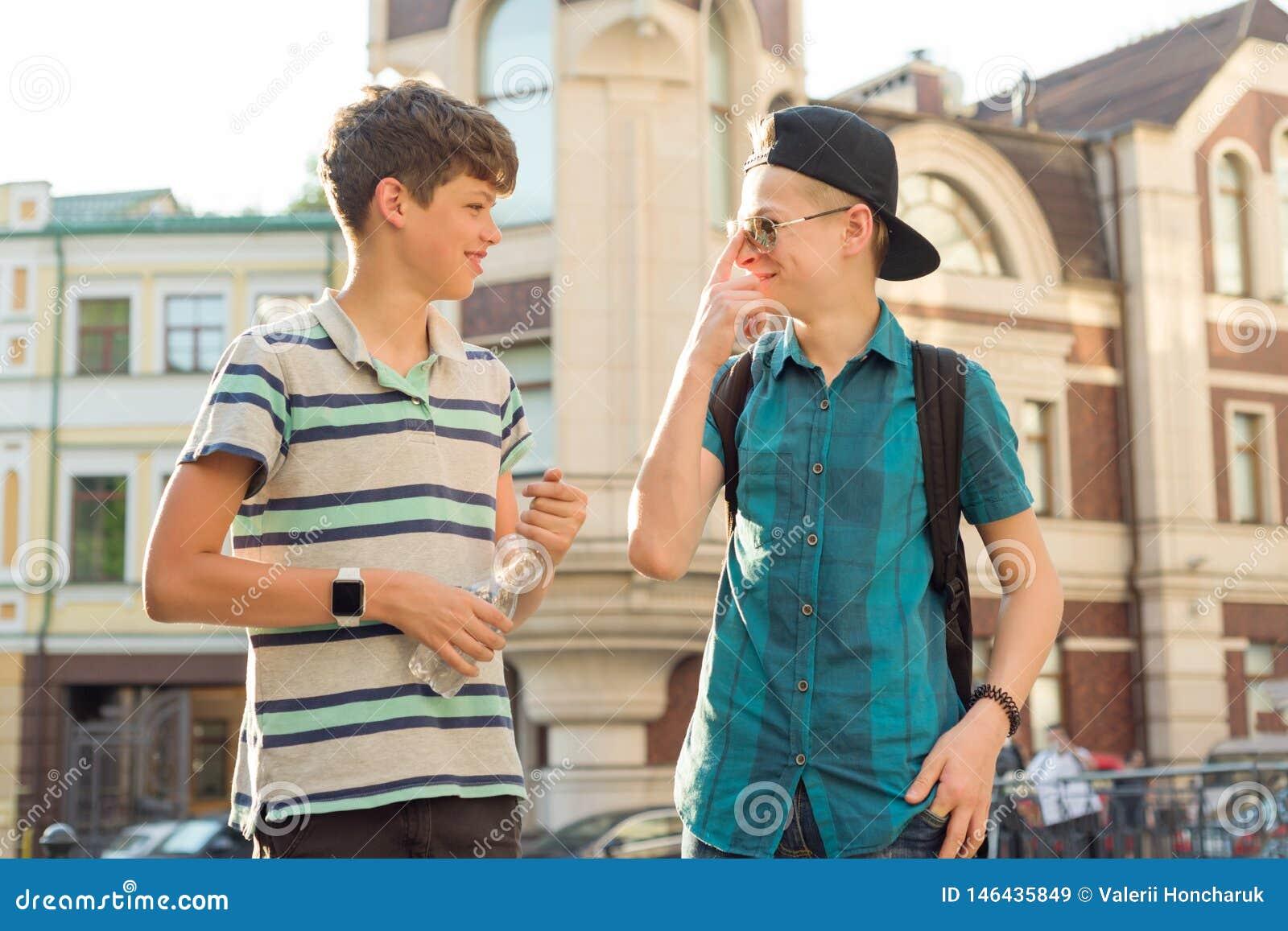 Retrato al aire libre de dos adolescentes 13 de los muchachos de los amigos, de 14 a?os que hablan y que r?en en la calle de la c
