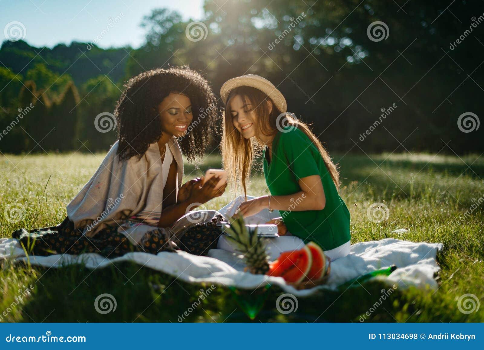 Retrato al aire libre de dos amigas multi-étnicas que pasan el tiempo junto en comida campestre en el prado soleado Los jóvenes