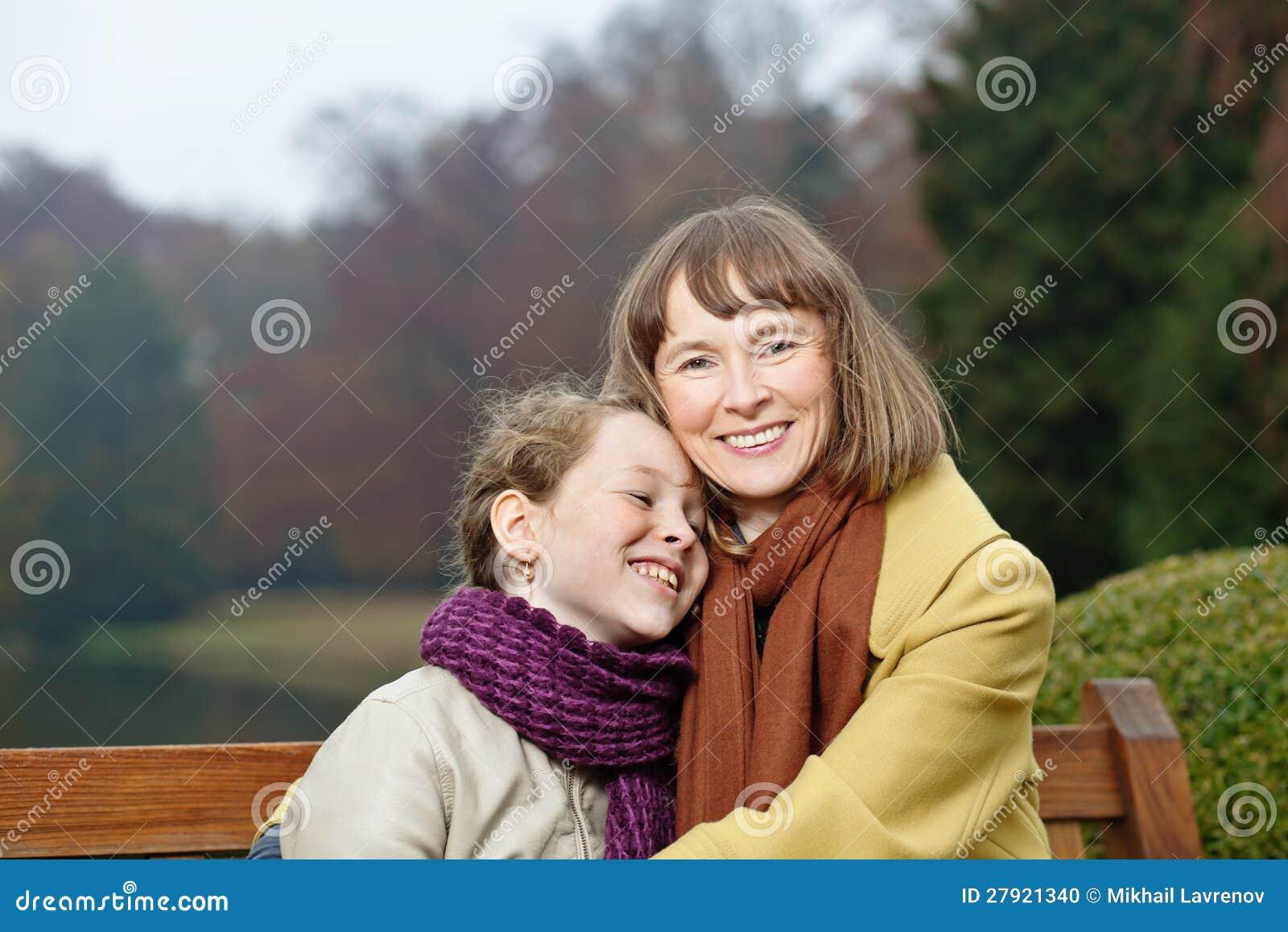 Retrato al aire libre de la mujer y de la muchacha sonrientes