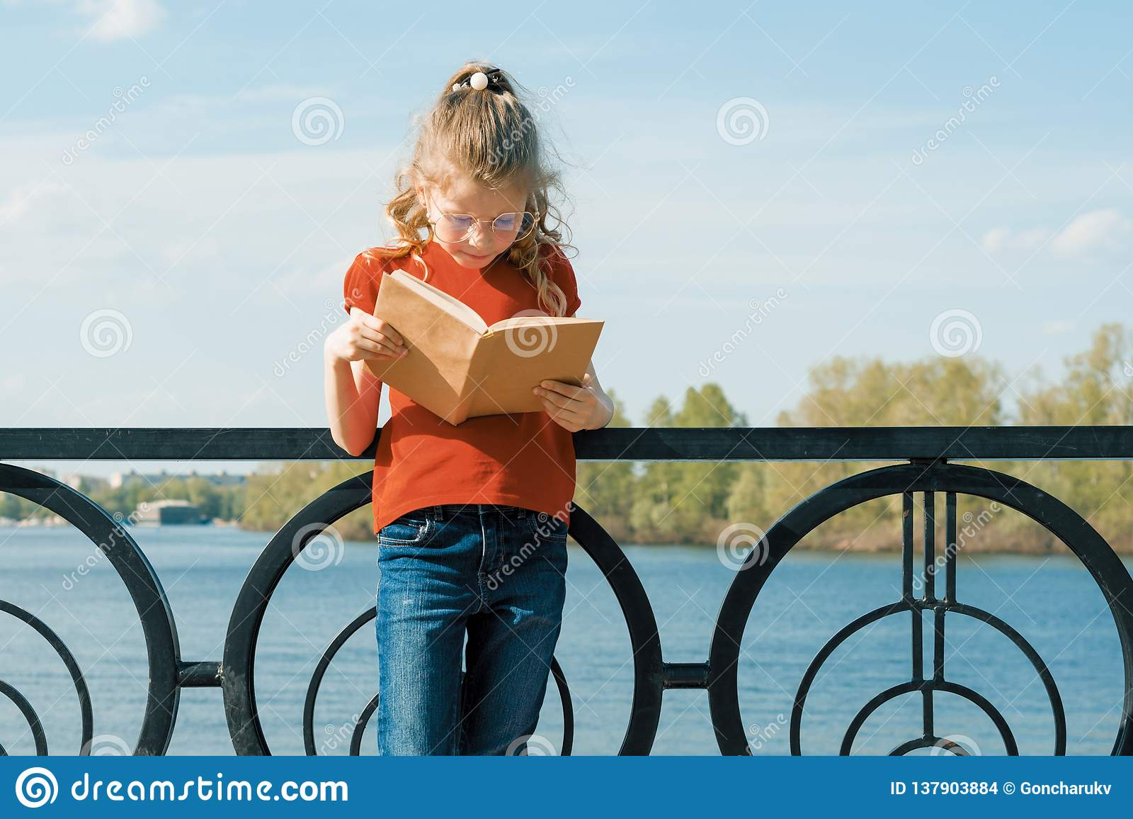 Retrato al aire libre de poca colegiala con el libro, niño 7, 8 años de la muchacha con los vidrios leyendo el libro de texto