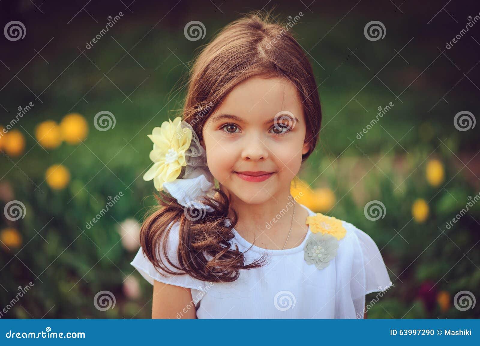 Retrato al aire libre del verano de la muchacha sonriente adorable del niño