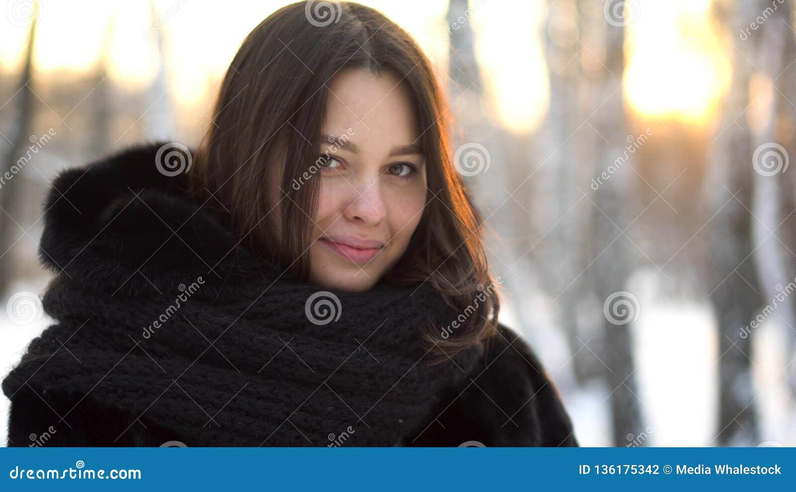 Retrato ascendente cercano de la muchacha morena hermosa en abrigo de pieles negro y la bufanda grande, hecha punto al aire libre