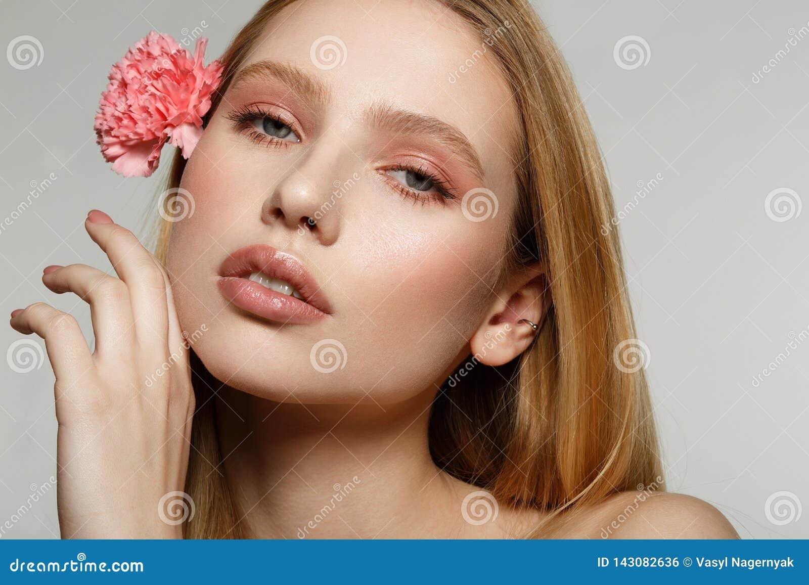 Retrato ascendente cercano de la muchacha rubia soñadora con el maquillaje de moda que toca su cara