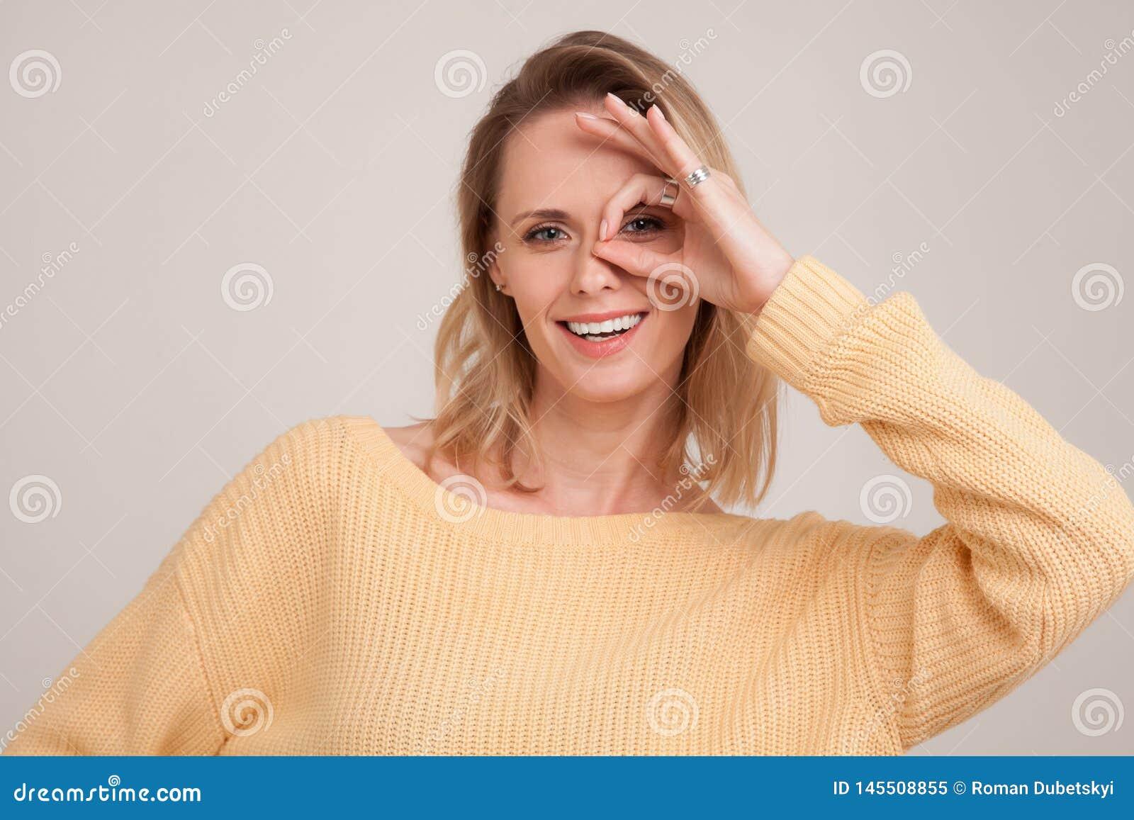 Retrato ascendente cercano de la mujer rubia sonriente con los dientes blancos, mirando la c?mara a trav?s de los fingeres en ges